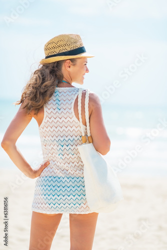 Relaxed woman in hat with bag on beach looking into distance