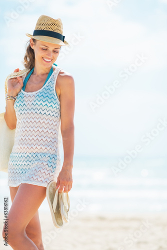 Young woman in hat with bag on beach