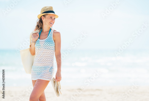 Smiling woman in hat with bag on beach looking on copy space
