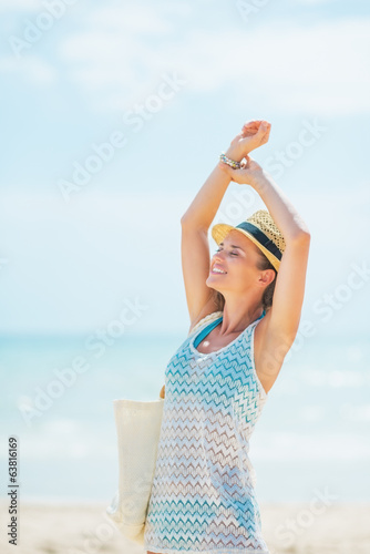 Happy young woman in hat with bag relaxing on beach