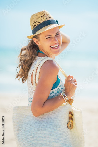 Portrait of smiling young woman in hat with bag on beach