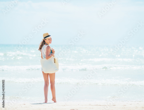 Young woman in hat with bag standing near sea
