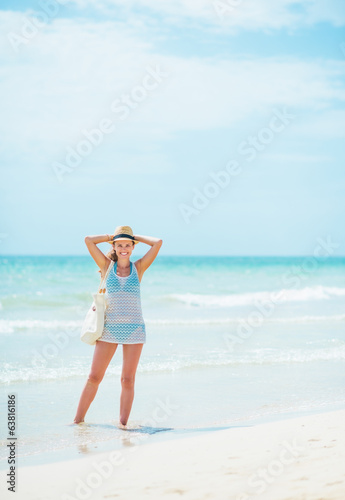 Full length portrait of young woman in hat with bag at seaside