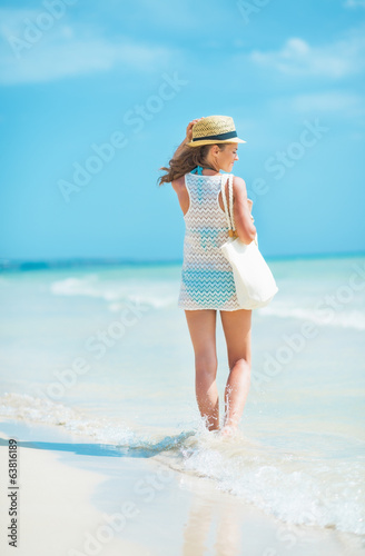 Young woman in hat with bag walking at seaside. rear view