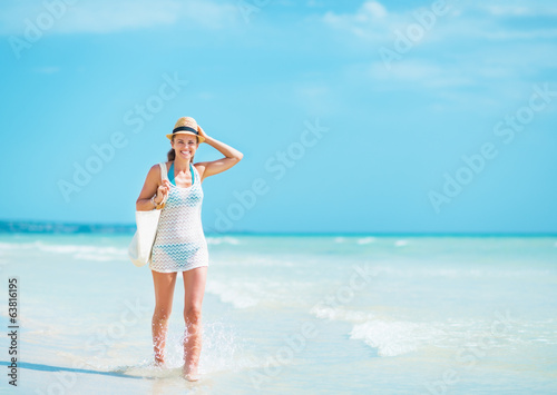 Happy young woman in hat with bag walking at seaside