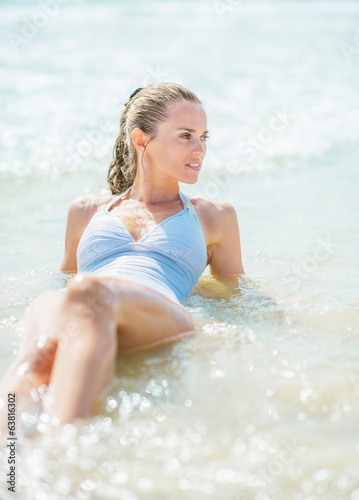 Happy young woman in swimsuit laying at seaside