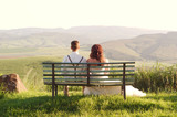 African bride and groom on bench with landscape