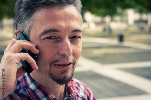 Man in short sleeve shirt talking on phone