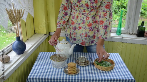 girl puts mint leaves glass cup pour water ceramic teaspoon