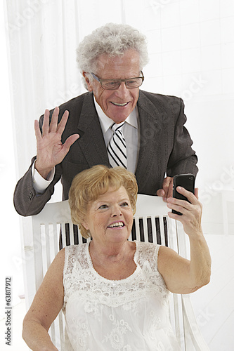 Smiling senior couple taking self portrait through smart phone
