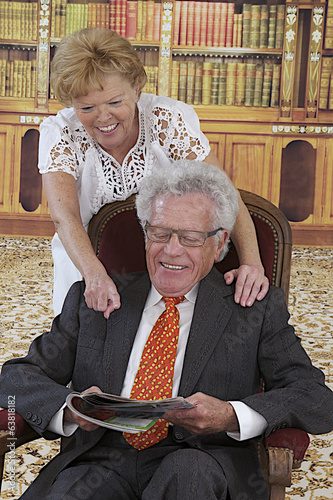 Senior couple reading magazine sitting on armchair