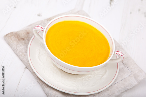 Carrot soup in a bowl, on the white table