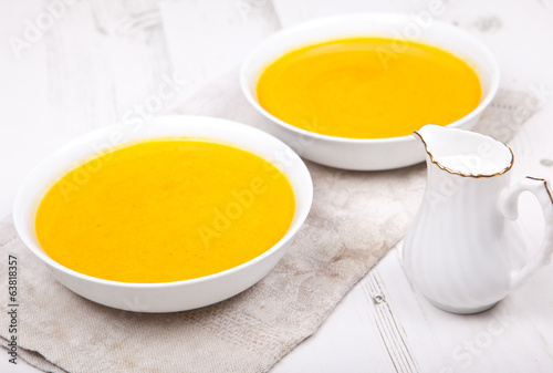 Spiced carrot soup in two bowls, on the white table