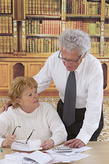 mature Couple Sitting in reading room  looking at  bills
