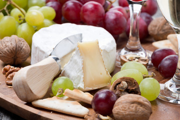 Camembert, a glass of red wine, grapes and crackers, close-up