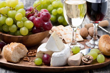Camembert, fresh baguette, grapes and wine on a wooden tray