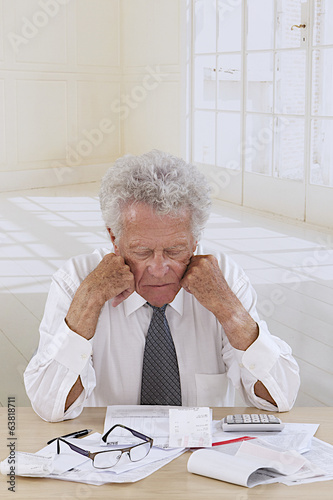Senior man  at desk holding  his head and worrying about money.