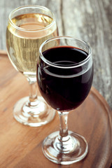 glass of red and white wine on a wooden board