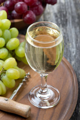 glass of white wine, corkscrew and grapes on a wooden board