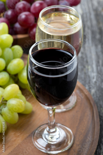 glass of red and white wine, grapes on a wooden board