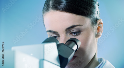 Female researcher using microscope close up