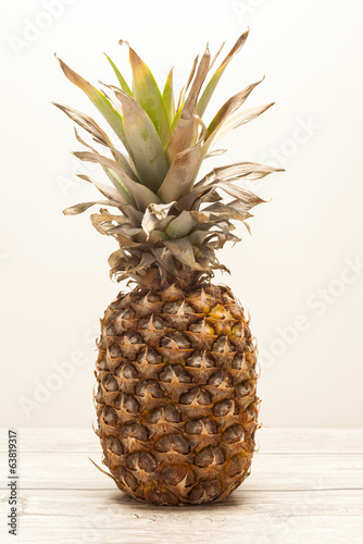 Single pineapple on wooden board