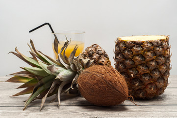 Coconut and half-cut pineapple on wooden board