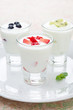 three yogurt with fruit in a glass beaker