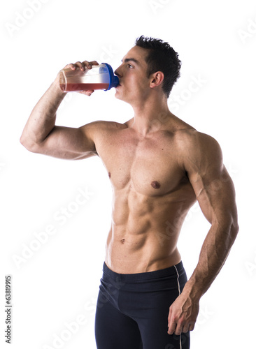 Muscular male bodybuilder drinking protein shake from blender