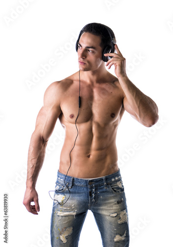 Muscular man standing, listening to music on headphones