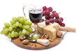 two glasses of wine, grapes and cheese on a wooden board