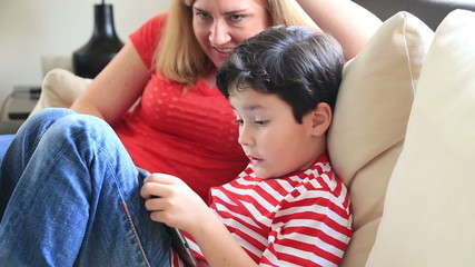 Mother And Son Using Digital tablet In The Living Room