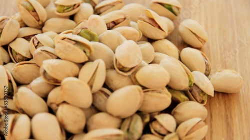 Roasted pistachios rotate on wood plate, video