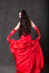 Latino Woman with long hair  in red waving dress dancing