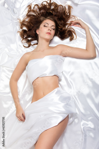 Young beautiful woman lying over white silk background