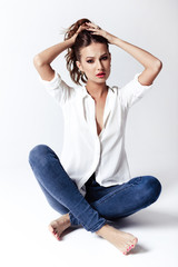 Fashion model sitting on a floor in a blouse and jeans barefoot