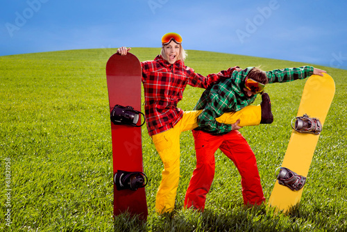 Couple in ski suit having fun with snowboards on the grass in gr