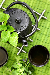 Tabletop with oriental teapot and cups with fresh herbs