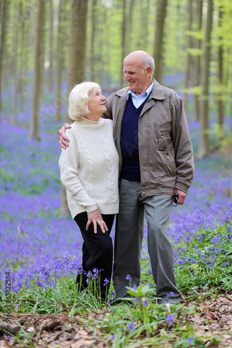 Loving senior couple hiking in blooming bluebells forest