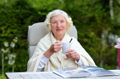 Happy senior woman relaxing in the garden drinking coffee