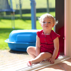 Little girl sitting at opened window with garden view