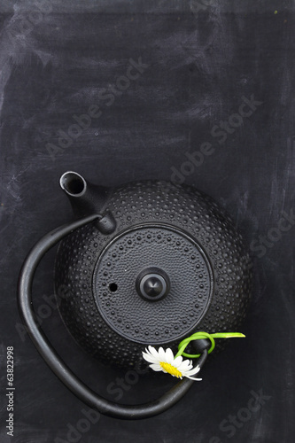 Teapot with chamomile on chalkboard top shot and copy-space