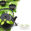 Teapot with fresh green herbs, flowers, cups and copy-space