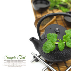Teapot with fresh green herbs, cups and copy-space
