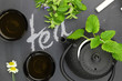 Teapot with herbs and teacups on chalkboard top shot