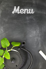 Teapot with herbs on chalkboard top shot with copy-space