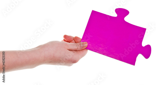 female hand holding big pink paper puzzle piece
