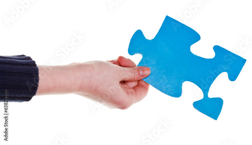 female hand holding big blue paper puzzle piece