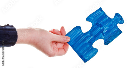 female hand with painted blue puzzle piece