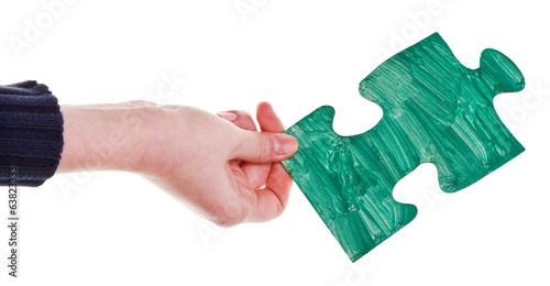 female hand with painted green puzzle piece